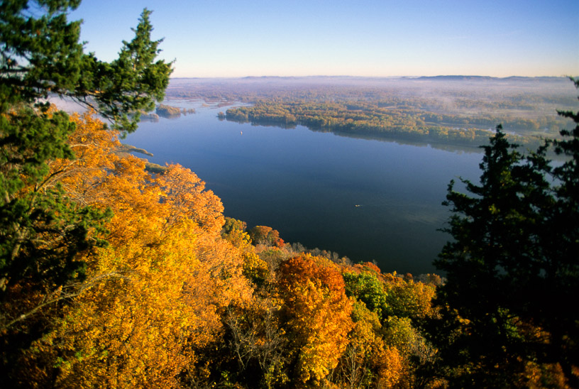 Fall scene of Mississippi River Valley in the mornig fog from scenic overlook in Great River Bluffs State Park near Winona.