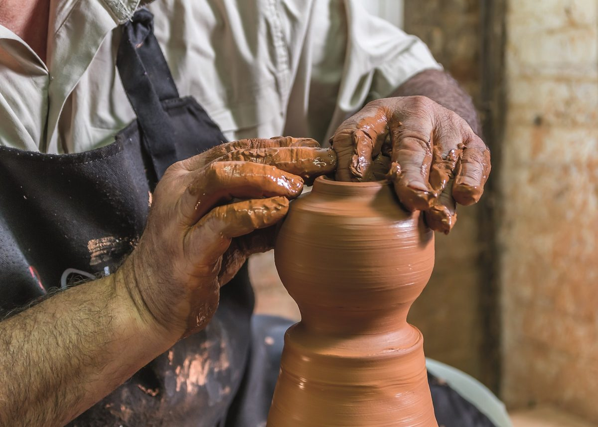 61987284 - close-up of the hands of a ceramist working in his potter wheel