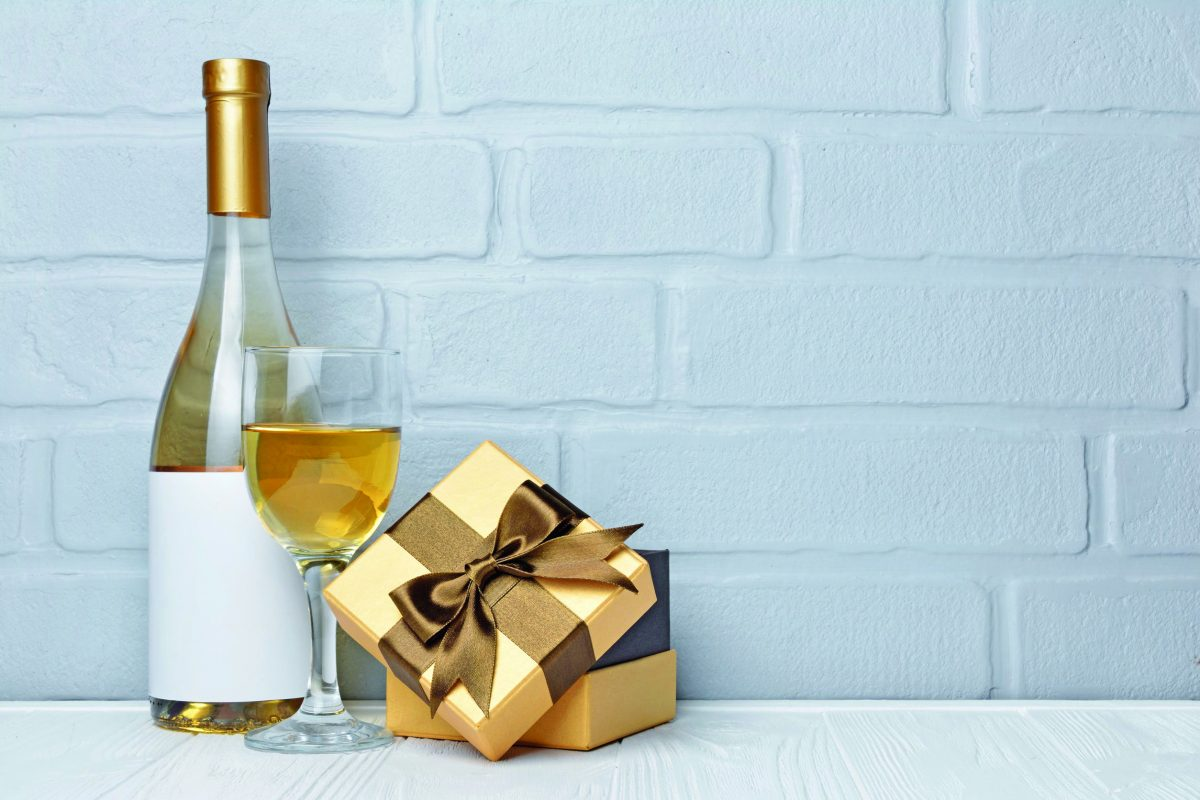 White wine bottle with empty label, glass for tasting and gift box for romantic surprise on gray brick wall background